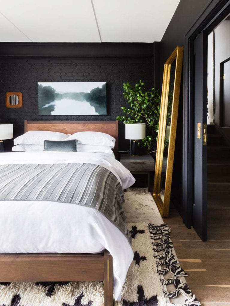 Moody black bedroom with walnut mid-century bed and gold floor mirror on Thou Swell @thouswellblog
