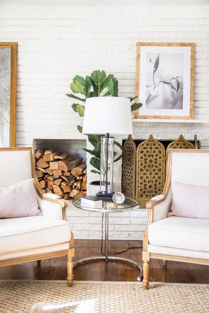 White brick fireplace with gold fireplace screen, stacked logs, linen armchairs, and pink pillows on Thou Swell @thouswellblog