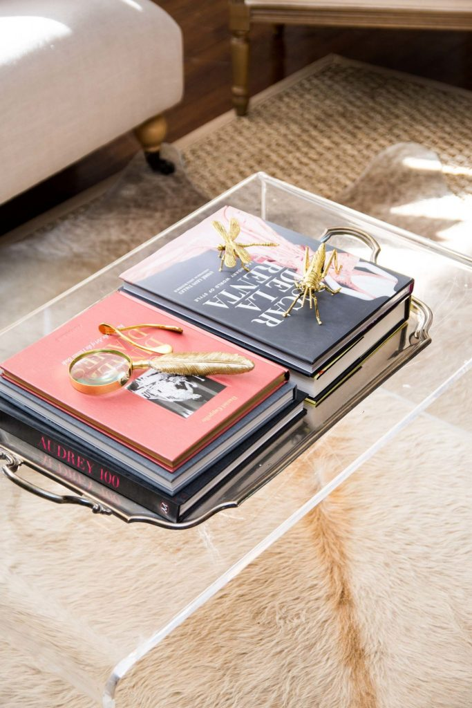 Lucite coffee table with coffee table books and gold decor on Thou Swell @thouswellblog