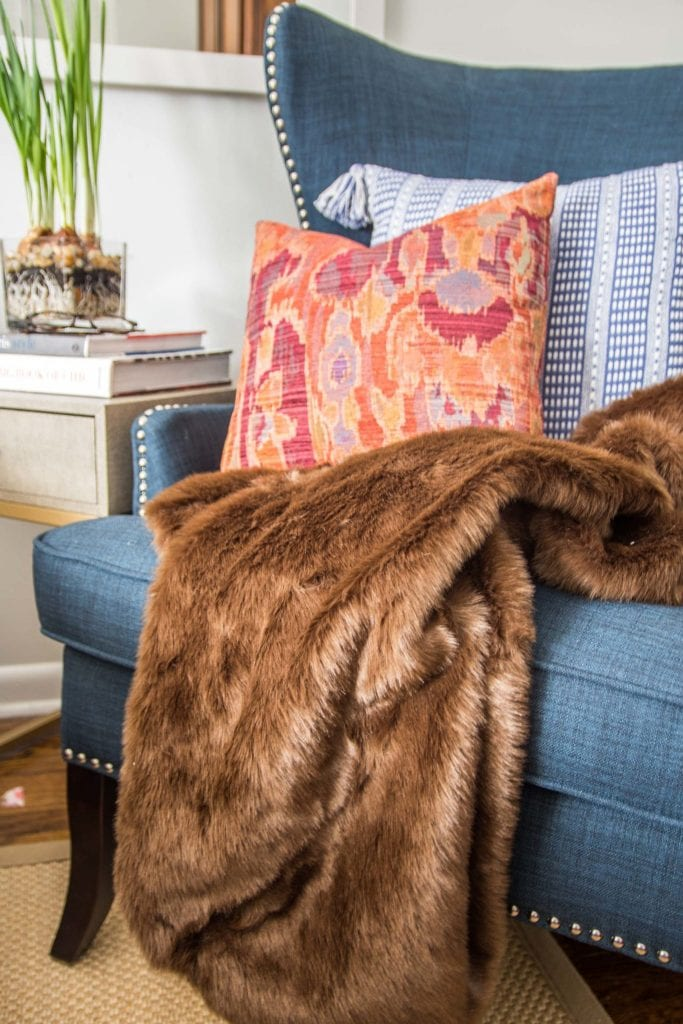 Brown faux fur throw and patterned pillows in a wingback accent chair on Thou Swell @thouswellblog