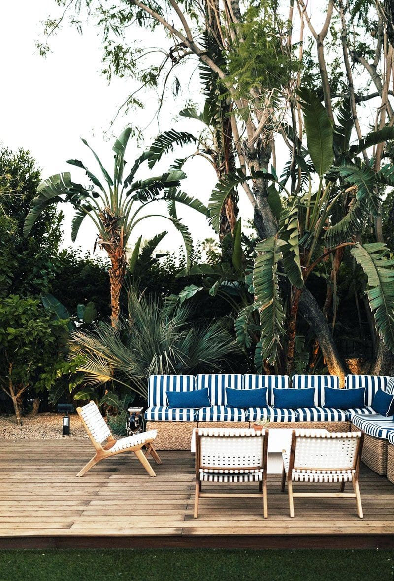 Tropical patio deck with white woven lounge chairs and blue-and-white striped sectional on Thou Swell @thouswellblog
