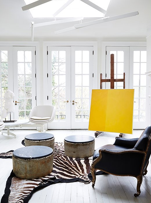 Stunning white sunroom with yellow painting and zebra rug on Thou Swell @thouswellblog
