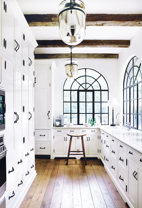 Beautiful black and white galley kitchen with arched iron windows and table lamp in the corner on Thou Swell @thouswellblog