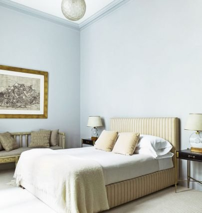 Simple bedroom with blue walls and striped upholstered bed on Thou Swell @thouswellblog