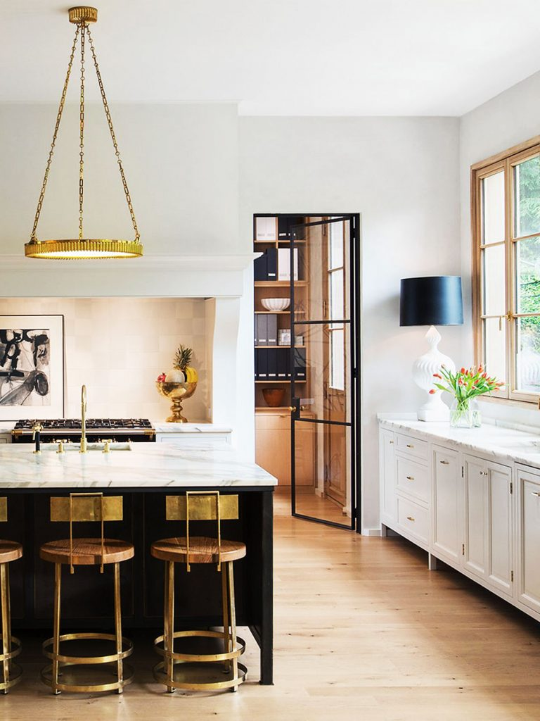 Beautiful modern kitchen with brass counter stools, pendant, and table lamp with black shade on Thou Swell @thouswellblog