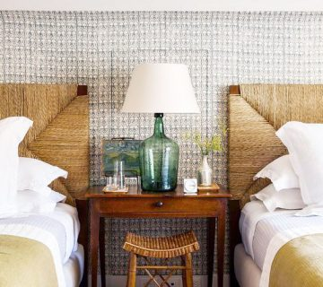 A classic, coastal twin bedroom with wicker headboards and a sea glass lamp on Thou Swell @thouswellblog
