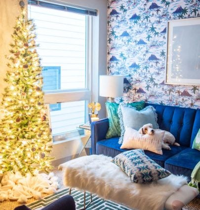 Playful apartment Christmas tree with whimsical blush ornaments and bird decorations in a tropical living room design on Thou Swell @thouswellblog
