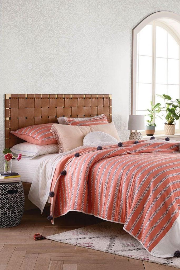 Modern boho bedroom design with pink pompom coverlet and white brick walls on Thou Swell #bohobedroom #bedroomdesign #pinkbedding