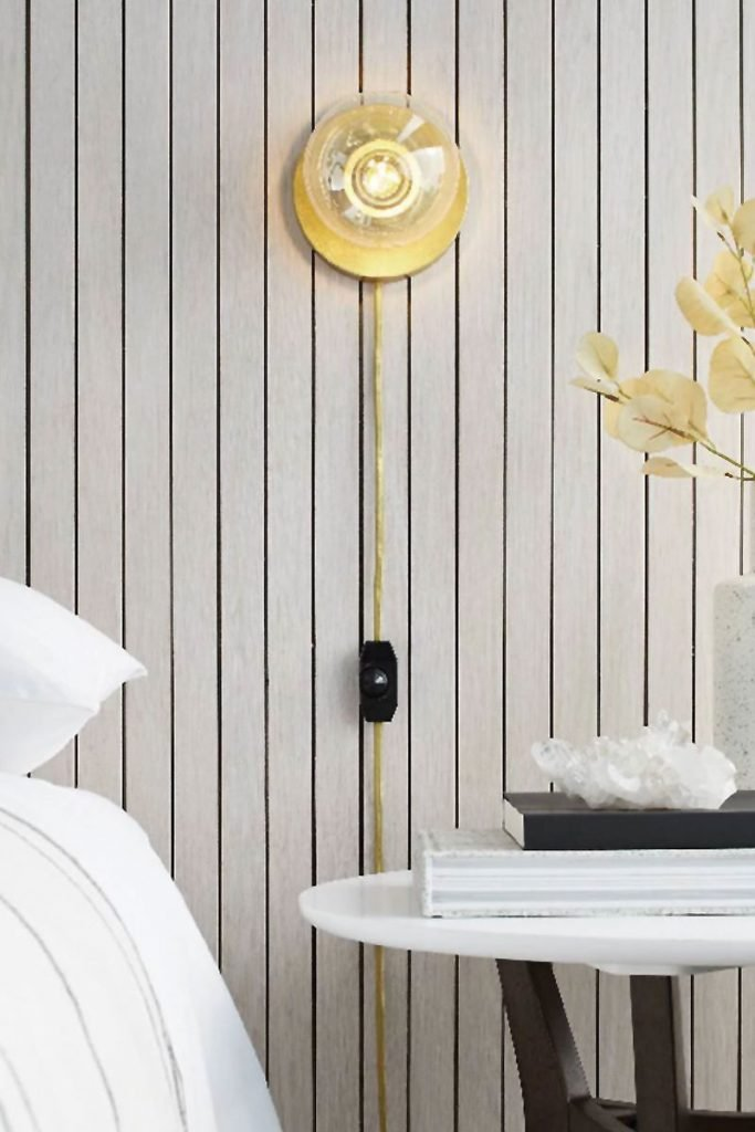 Modern bedroom styling with single bulb sconce and paneled wall on Thou Swell #minimaldecor #minimalstyle #bedroomstyling