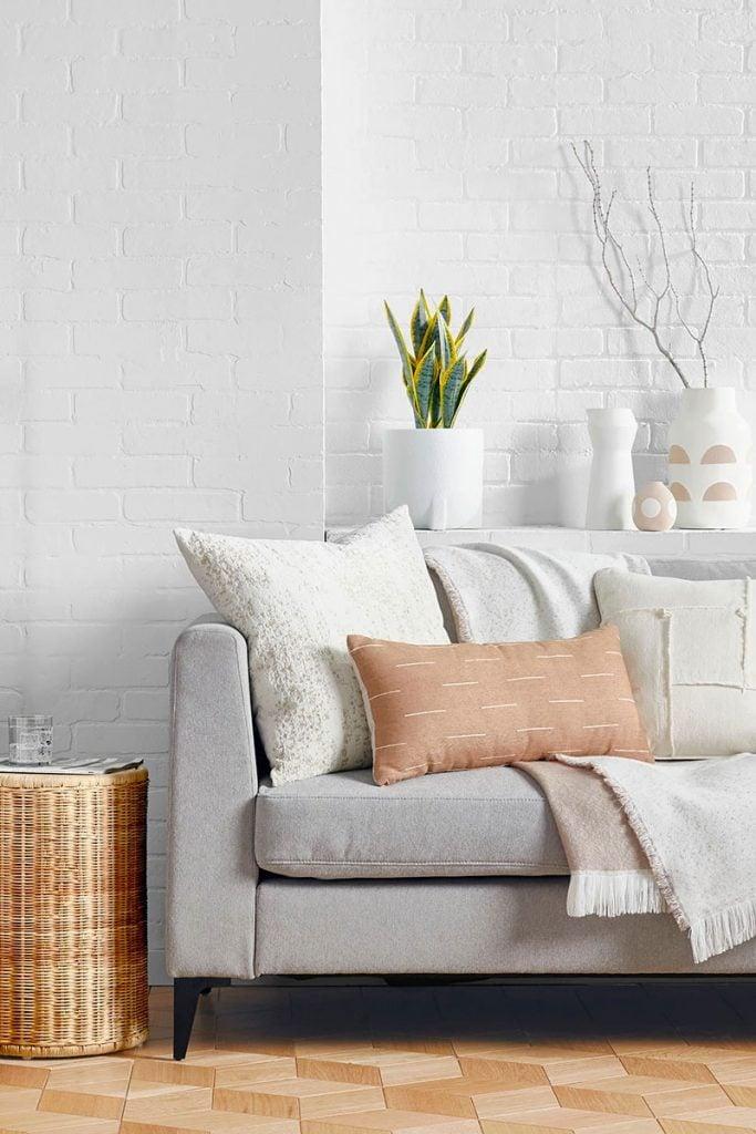 Modern white living room with neutral pillows and grey sofa on Thou Swell #modernlivingroom #livingroomdesign #livingroomdecor