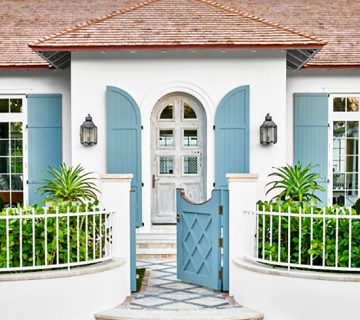 Stucco beach house exterior with blue shutters in Palm Beach on Thou Swell #hometour #palmbeach #exterior #coastaldecor