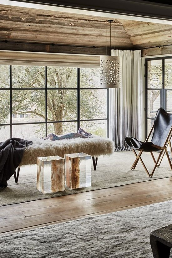 Master bedroom seating area with leather sling chair and fur bench with clear cube tables on Thou Swell #livingroom #livingroomdesign #austinhome #hometour