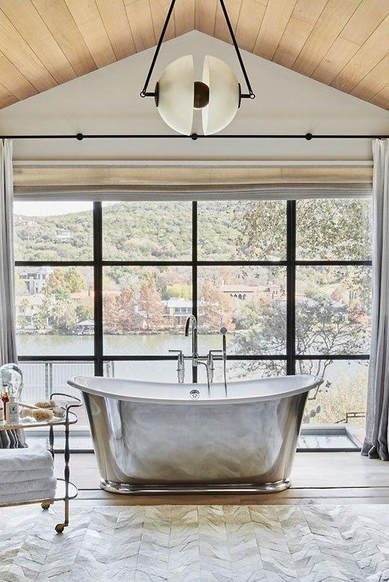 Luxury master bathroom design with steel window and silver chrome polished bathtub on Thou Swell #livingroom #livingroomdesign #austinhome #hometour