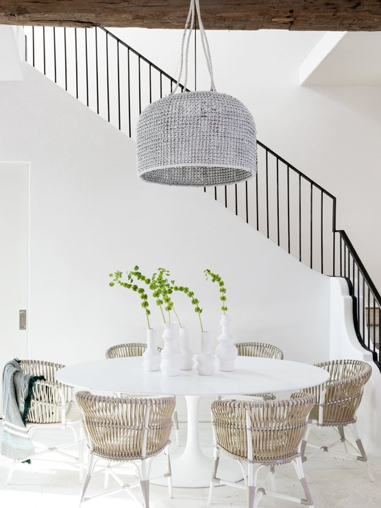 Modern minimal white dining room design with wicker chairs and Saarinen table on Thou Swell #saarinentable #diningroom #diningroomdesign #coastaldining #coastaldecor #wicker