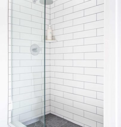 Master bathroom shower tile renovation with grey herringbone mosaic and white subway tile on Thou Swell #bathroom #masterbathroom #showertile #subwaytile #herringbonetile #walkinshower #shower
