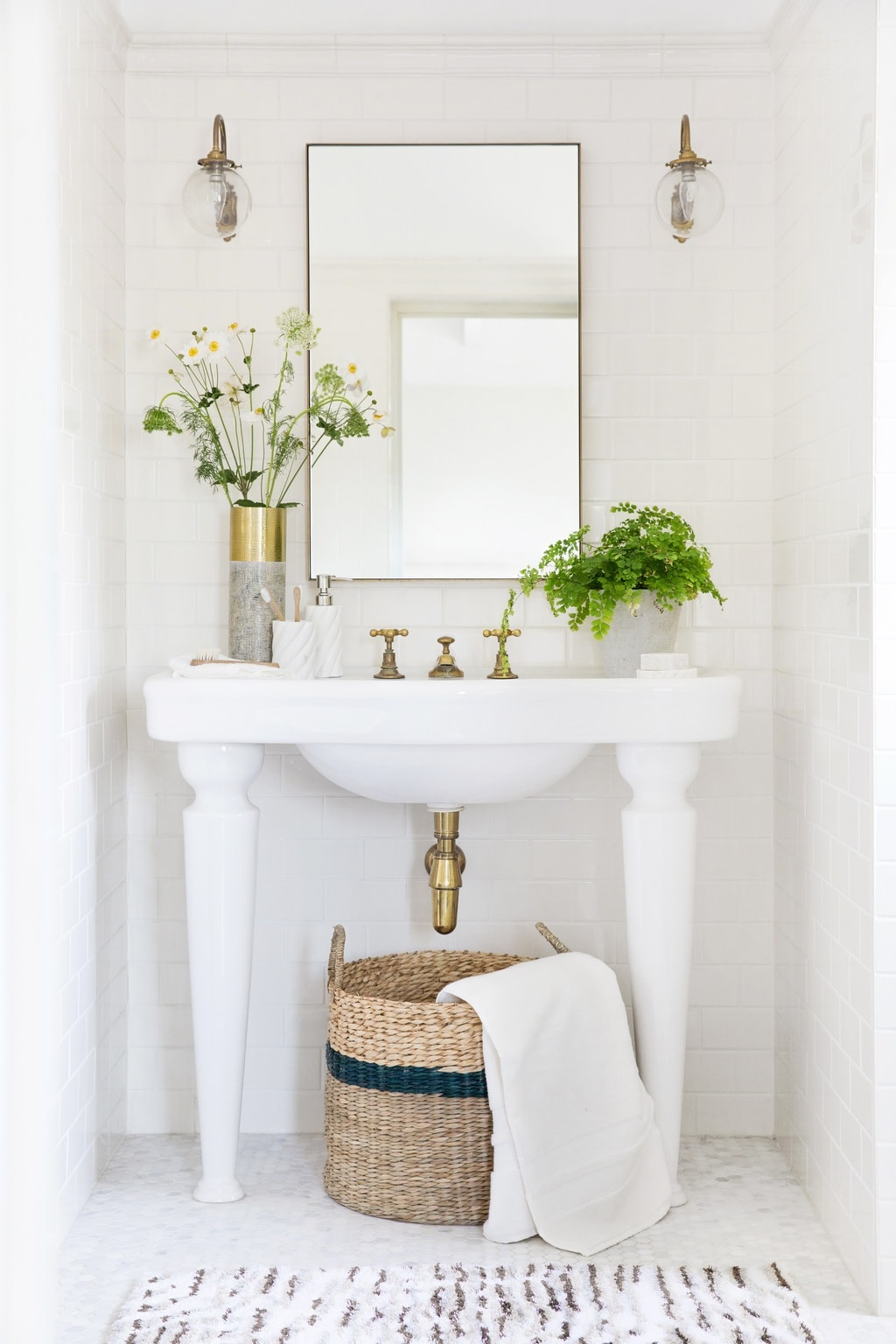 Classic white bathroom with subway tile, fern, glass sconces, and wicker basket storage on Thou Swell @thouswellblog #bathroom #bathroomdesign #classicbathroom #classicdesign #interiordesign