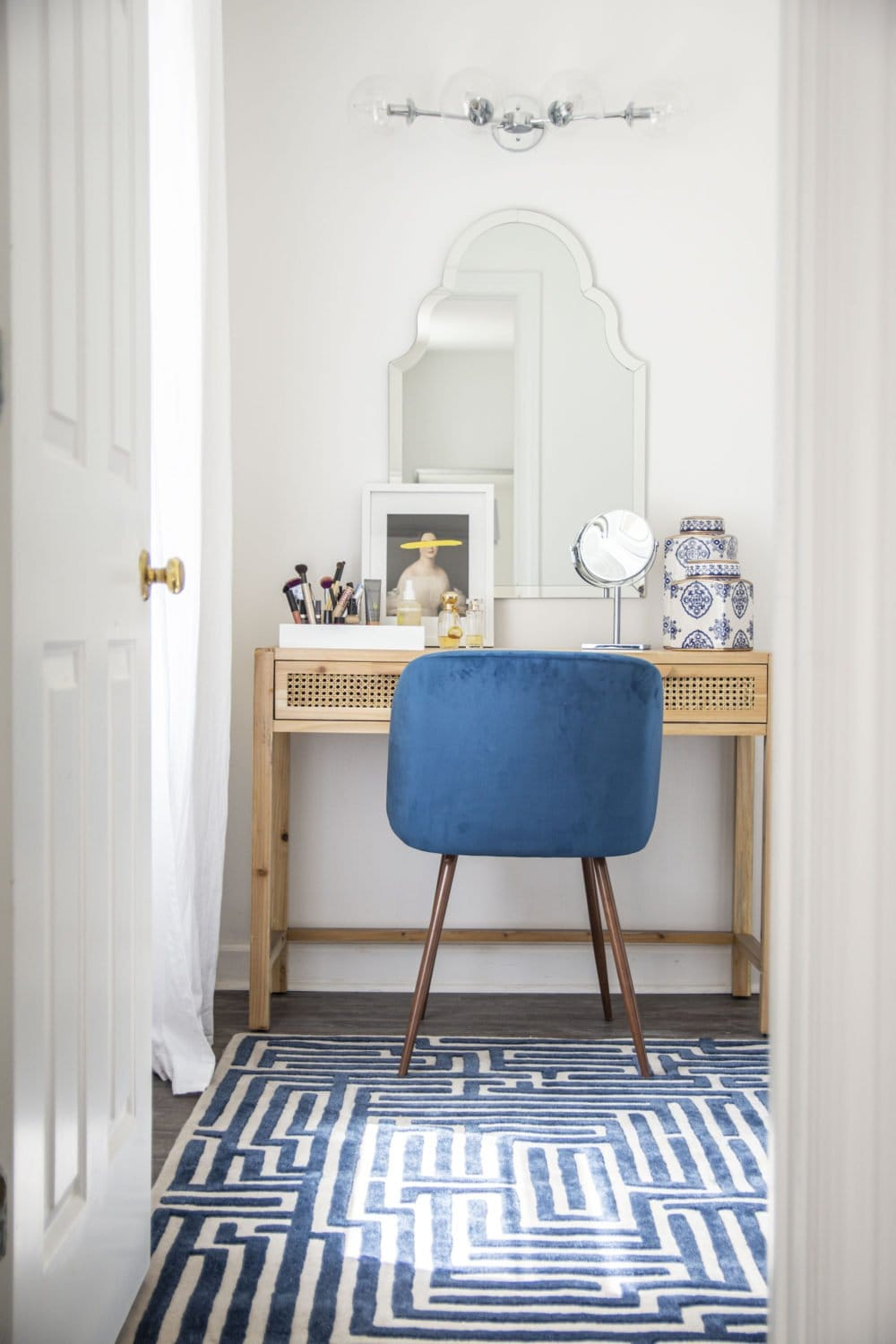 Blue and white vanity room in master suite with cane console desk, blue velvet chair, and Moroccan mirror on Thou Swell @thouswellblog #vanity #vanityroom #vanitydesign #masterbedroom #mastersuite #interior #interiordesign