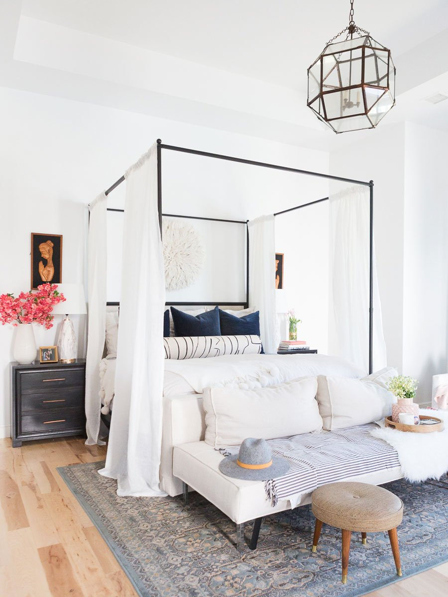 Bright and playful master bedroom design with canopy bed, white curtains, upholstered bench, and grey area rug on Thou Swell @thouswellblog #bedroom #bedroomdesign #masterbedroom #bedroomdecor #jujuhat #interiordesign