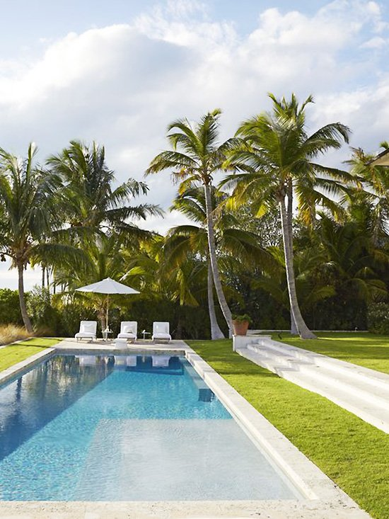Lap pool in Bahamas with palm trees and lounge chairs on Thou Swell #bahamas #pool #lappool #loungechairs #palmtrees #beachhouse