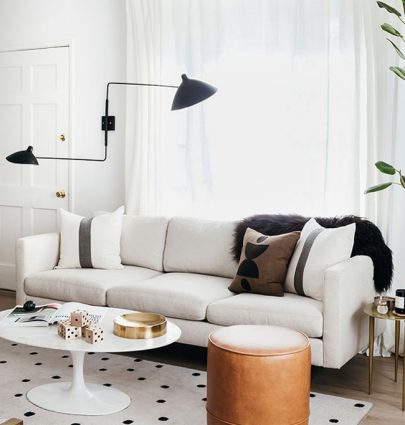 Modern living room with white sofa, leather stool, Saarinen marble coffee table, spotted rug, and black two-arm sconce on Thou Swell @thouswellblog #livingroom #moderndesign #modernroom #moderninterior #interiordesign #whitesofa #modernlivingroom