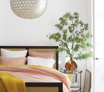 Pink and yellow bedding in modern bedroom with cane wicker bed and capris shell chandelier on Thou Swell #bedroom #bedroomdesign #bedroomstyle #pinkandyellow #homedecor
