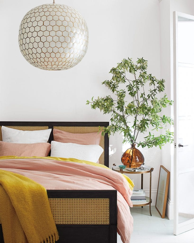 Pink and yellow bedding fall home decor with cane wicker bed and capiz shell chandelier on Thou Swell #bedroom #bedroomdesign #bedroomstyle #pinkandyellow #homedecor