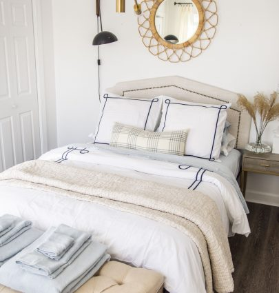 Guest room decor and bedding with tan quilt, blue sheets, and white duvet from Serena & Lily best-in-class bedding on Thou Swell by Kevin O'Gara #bed #bedding #bedroom #bedroomdecor #guestroom #guestbedroom #serenaandlily #sheets #bedroomideas #homedecor #homedecorideas