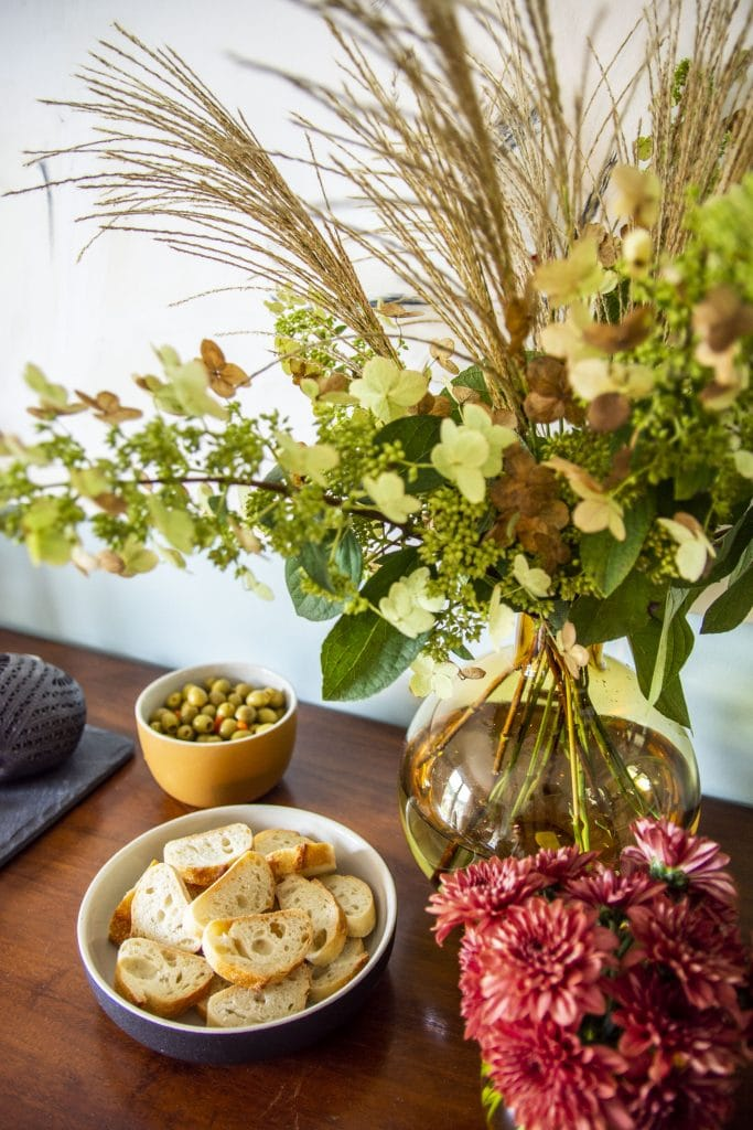 Chic halloween party decor with flowers and cheese board by Kevin O'Gara on Thou Swell #halloween #halloweenparty #halloweendecor #halloweenflowers #cheeseboard #cheese #flowers #partydecor #party #decor #decorideas
