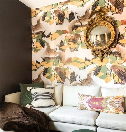 Brown study living room design with sectional, Cranes wallpaper, vintage gold mirror, and green ottomans on Thou Swell #livingroom #livingroomdesign #study #studydesign #wallpaper #brownwalls #sectional