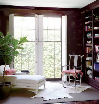 Brown walls with high-gloss lacquer finish in a living room library in New Orleans on Thou Swell #brown #brownwalls #brownpaint #livingroom #livingroomdesign #homedesign #neworleans #interiordesign #traditionaldecor