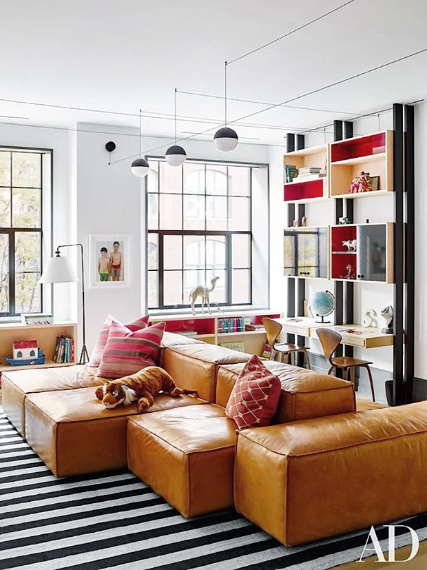 Leather modular sectional in New York City playroom via Architectural Digest on Thou Swell #playroom #livingroom #sectional #leathersectional #leathersofa #playroomdesign #kidsroom