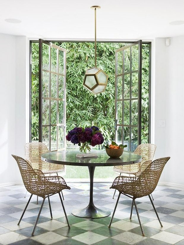 Modern dining room in Hollywood, California designed by Nate Berkus with tulip table, rattan chairs, steel doors, and marble floor on Thou Swell #diningroom #dining #modernroom #moderndining #tuliptable #marblefloor #steeldoors #california #californiastyle