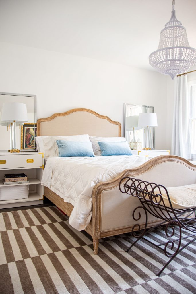 Master bedroom design with french-style upholstered bed, iron bench, and campaign nightstands in white with striped rug by Kevin O'Gara on Thou Swell #bedroom #masterbedroom #bedroomdesign #bedroomdecor #masterbedroomdesign #neutralbedroom #luxurybedroom #interiordesign #homedesign #homedecor
