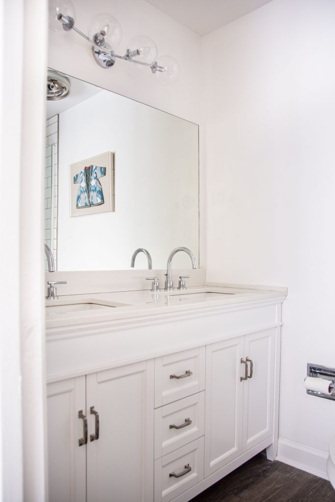 White bathroom renovation with new vanity, faucets, and lighting on Thou Swell #bathroom #bathroomdesign #whitebathroom #masterbathroom