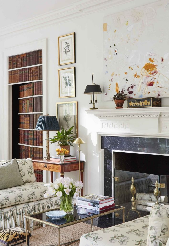 Secret bookcase door in traditional living room by Caroline Gidiere in Mountain Brook with fireplace mantel and abstract painting on Thou Swell #secretdoor #livingroom #livingroomdesign #fireplace #fireplacemantel #mantel #bookcasedoor #librarydoor