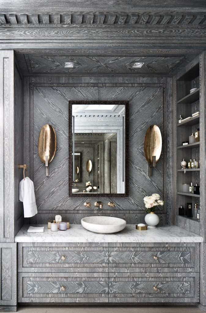 Grey cerused wood bathroom sink vanity with copper sconces and built-in shelves by Russian interior designer Catherine Fedorchenko on Thou Swell #bathroom #bathroomdesign #cerusedwood #custombathroom #luxurybathroom #luxurydesign #luxuryinterior #interiordesign