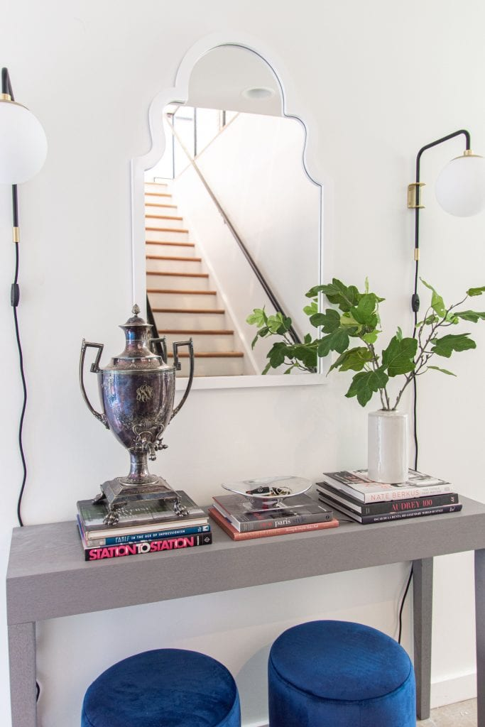 Modern entry design with AllModern grey console table, blue velvet stools, and sconce lights on Thou Swell #entry #entryway #entrywaydesign #entrywaydecor #entrydesign #allmodern