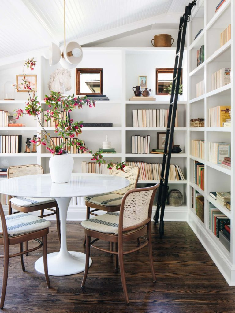 Bookshelves with ladder, shelf styling in dining nook with tulip table and home decor accessories on Thou Swell #shelfladder #bookshelves #builtinshelves #shelfstyling #homedecor #homedecorideas #decorhaul