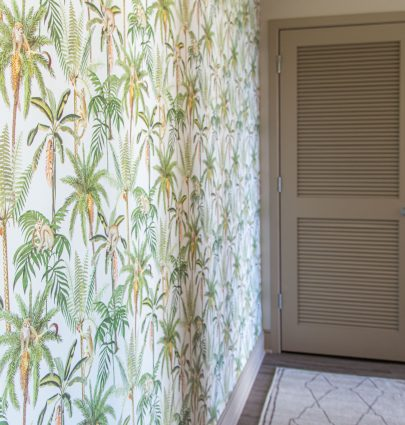 Tropical leaf and monkey wallpaper by Walls Republic in an apartment entryway accent wall on Thou Swell #homedecor #homedecorideas #wallpaper #tropicalwallpaper #monkeys #accentwall #wallsrepublic