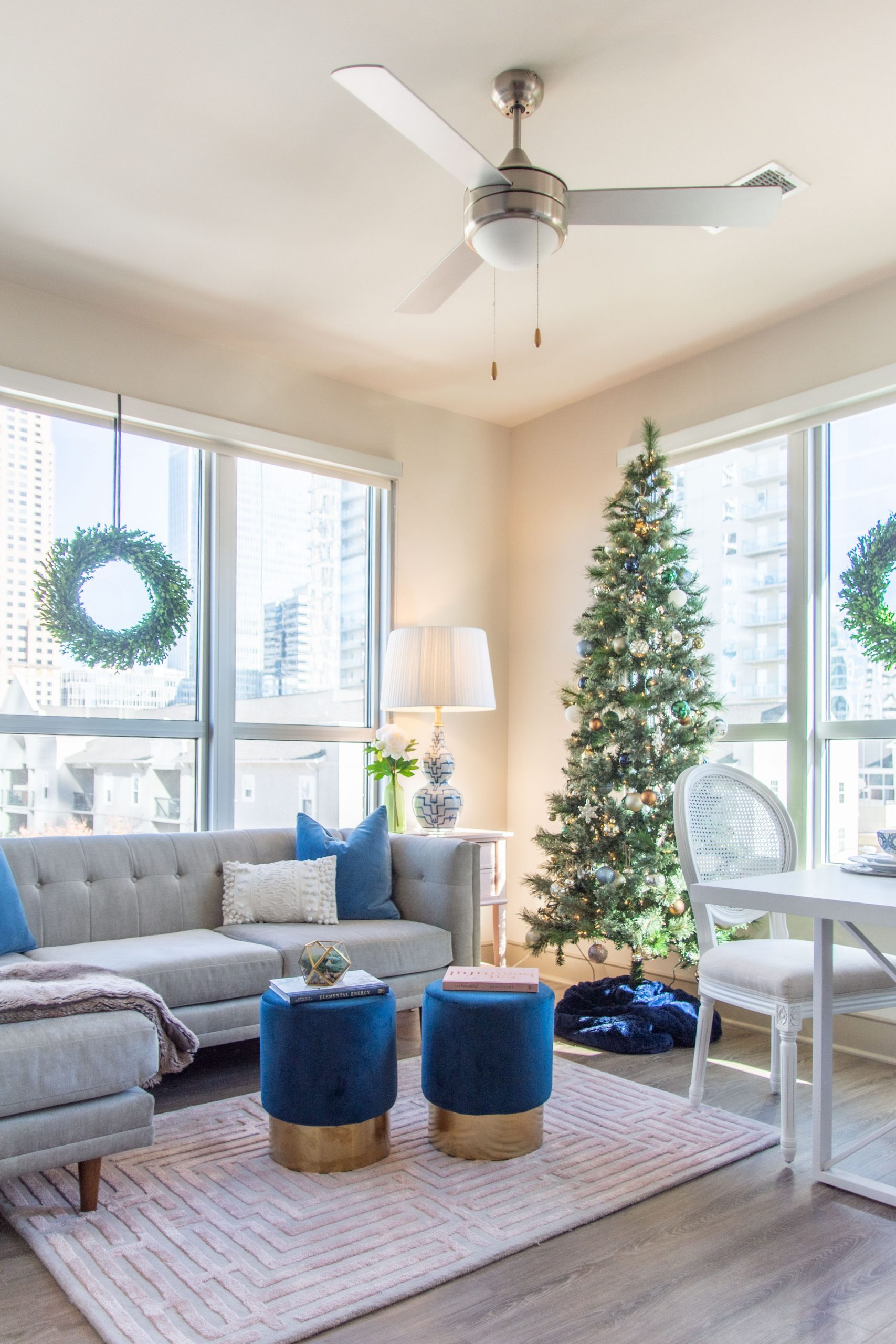 Apartment living room Christmas tree holiday decor with pink and blue, maze rug, velvet stools, and tan sectional by Kevin O'Gara on Thou Swell #apartmentstyle #apartmentdesign #apartmentdecor #livingroom #livingroomdesign #livingroomdecor #christmastree #holidaydecor #christmastyle #homedecorideas