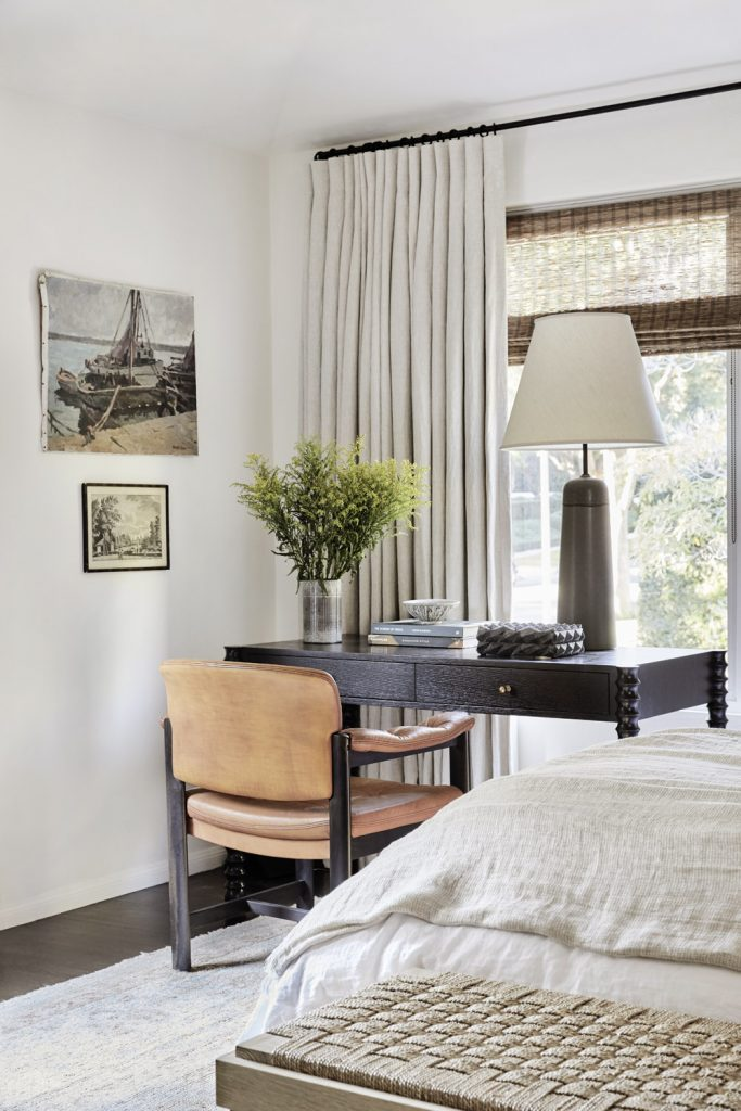 Master bedroom design with vintage table lamp, leather armchair, black desk, and painting wall art on Thou Swell #bedroom #bedroomdesign #masterbedroom #homedecor #homedesign #vintageart #vintagelamp #vintage #vintagestyle