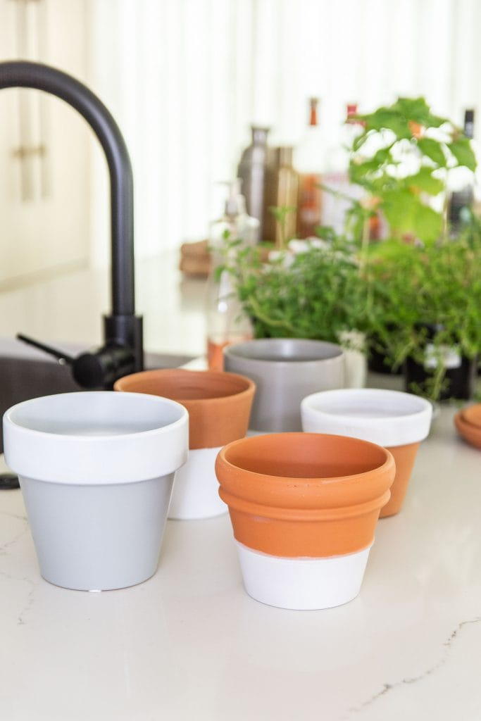 Indoor countertop herb garden in the kitchen with mismatched pots and Plasti Dip Craft coating DIY project on Thou Swell #herbgarden #indoorplants #indoorgarden #kitchengarden #plastidip